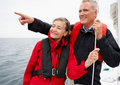 Cute senior couple on a sea voyage, pointing away Stock Image