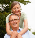 Cute senior woman with arms around husband Royalty Free Stock Photos
