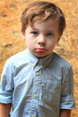 Cute serious kid a closeup of a year old child with brown hair wearing a button up shirt shallow dof Stock Photography