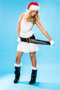 Cute sexy blond woman in a santa hat and costume celebrating christmas pulling on the broad black belt to emphasise her shapely Stock Photos