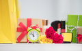 Cute shopping bag, make up set, gifts, alarm clock and roses on Royalty Free Stock Photo