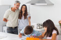 Cute siblings drawing together in kitchen with their parents smi smiling at home Stock Photography
