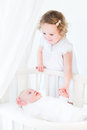 Cute siblings little toddler girl and newborn baby with curly hair wearing a white dress Stock Photo