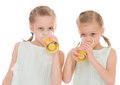 Cute sisters drink from a glass of fresh orange juice isolated on white background Stock Photos