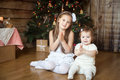 Cute sisters in front of decorated Christmas tree Royalty Free Stock Photo