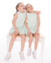 Cute sisters having fun sitting on a chair isolated white background Royalty Free Stock Image