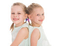 Cute sisters having fun sitting on a chair isolated white background Stock Photos