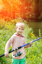 Cute small boy stand near a river with a fishing rod in his hands. Royalty Free Stock Photo
