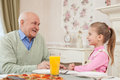 Cute small girl is dining with her grandparent portrait of cheerful child visiting grandfather they are sitting at the table and Royalty Free Stock Images