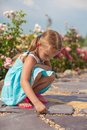 Cute small girl drawing on the sidewalk with chalk Royalty Free Stock Photo