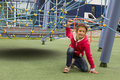 Cute small mixed race girl using a slide at a colorful playground Royalty Free Stock Photo