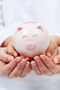 Cute small piggy bank in child hands upheld by adult financial education concept Stock Images