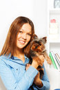 Cute small yorkshire terrier with smiling woman brown holding him hands indoors Royalty Free Stock Photography