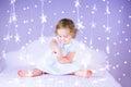 Cute smiling baby girl on bed between beautiful purple lights