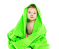 Cute smiling baby under the bright green towel