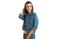 Cute smiling brunette stands in jeans jacket smiles and holds her hand near the head