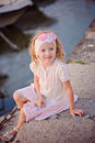 Cute smiling child girl in pink outfit portrait sitting on sea side vertical Royalty Free Stock Photography