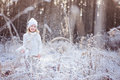 Cute smiling child girl on the walk in winter frozen forest white outfit Royalty Free Stock Image