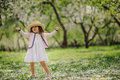 Cute smiling dressy baby girl on the walk in blooming cherry garden in spring cozy rural scene happy childhood concept Stock Image