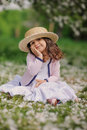 Cute smiling dressy baby girl on the walk in blooming cherry garden in spring cozy rural scene happy childhood concept Stock Photos