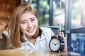 Cute smiling girl with alarm clock on wooden table