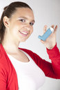 Cute smiling girl with asthma inhaler using an for preventing attacks Royalty Free Stock Image