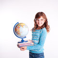 Cute smiling girl holding books and globe on white portrait of kid stack of with Royalty Free Stock Image