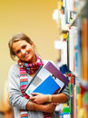 Cute smiling lady holding books in library Stock Photography
