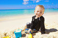 Cute smiling little boy playing sand sunny beach vacation his family Stock Photos