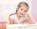 Cute smiling little girl drawing with paint and paintbrush Royalty Free Stock Photo