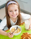 Cute smiling little girl eating her breakfast in the kitchen Royalty Free Stock Photo