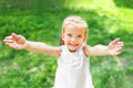 Cute smiling little girl giving her hands on the meadow Stock Photography