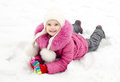 Cute smiling little girl lying on snow in winter day outdoor Royalty Free Stock Photography