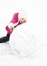 Cute smiling little girl makes snowman in winter day outdoor Stock Photos
