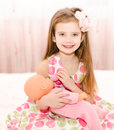 Cute smiling little girl playing with a doll at home Stock Photography
