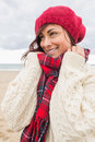 Cute smiling woman in warm clothing looking away at beach young stylish on the Stock Images