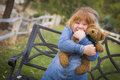 Cute smiling young girl hugging her teddy bear outside on bench Stock Photos