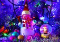 Cute snowman and santa claus in glass ball on colored blurred b Royalty Free Stock Photo