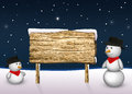 Cute snowmen with a blank wooden sign are looking to in snowy winter scene Stock Photos