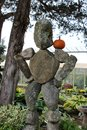 Cute stone sculpture with small pumpkin balanced on shoulder, seen at popular nursery Connecticut, 2018 Royalty Free Stock Photo