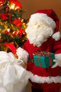 Cute stuffed toy Santa Claus giving a Christmas present. Royalty Free Stock Photo