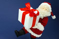 Cute stuffed toy Santa Claus hurrying with large Christmas prese Royalty Free Stock Photo