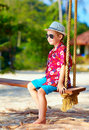Cute stylish boy on swings on the beach portrait of Stock Image