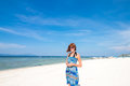 Cute stylish girl in blue dress standing on the amazing beach with wite sand, holding smartphone in her hands. She has Royalty Free Stock Photo
