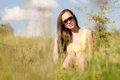 Cute summer girl having a rest outdoor portrait of sitting in high green grass and wearing huge sunglasses Stock Photography