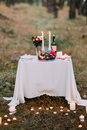 Cute table with many burning candles for romantic dinner at the autumn forest Royalty Free Stock Photo