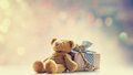 Cute teddy bear, golden key and beautiful gift on the fairy ligh Royalty Free Stock Photo