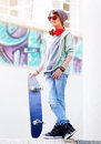 Cute teen boy with skateboard outdoors standing on the street different colorful graffiti on the walls hipster style cool Royalty Free Stock Photography