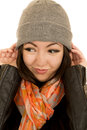 Cute teen female model wearing beanie looking away teenage adjusting her from camera Stock Photos