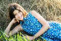 Cute teen girl in blue dress sitting on the farm hay background Royalty Free Stock Image